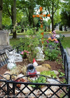 No one special, but someone clearly cares enough to populate their grave with gnomes.