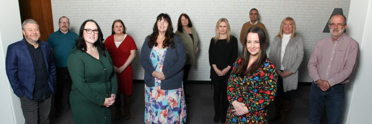WELL Training directors Lianne Russell, third left, Jackie Wyke fifth left, CEO Lindsey Flynn, front right, and Paul Kennedy, far right