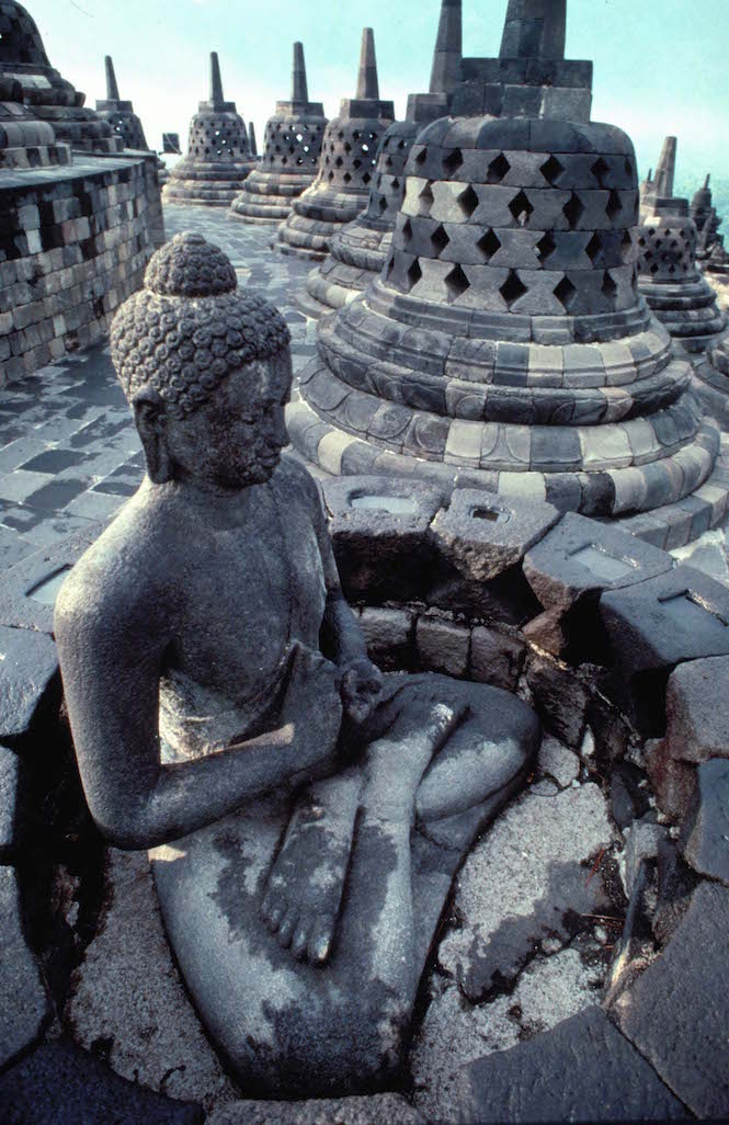 A stone Buddha sits atop the incredible Borobudur temple -Image credit Andrew Marshall