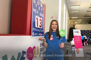 WeLoveU volunteer holds a sign with a B+ blood type