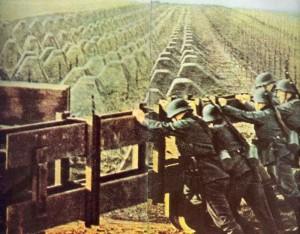 Deutsche Soldaten schließen das Tor an einer Panzersperre aus Betonklötzen am Westwall
