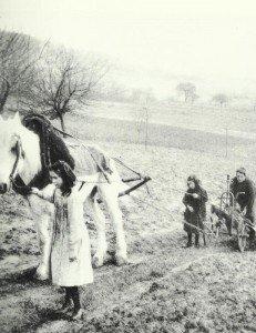 Frauen und Kinder beim Pflügen