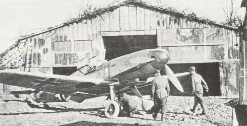 Bf 109 F steht vor einem als Scheune getarnten Hangar