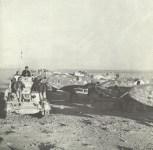 britischer Panzer passiert zerstörte italienische Flugzeuge