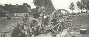 Deutsche Artilleristen sitzen an der Ostfront neben ihrem 77-mm-Feldgeschütz