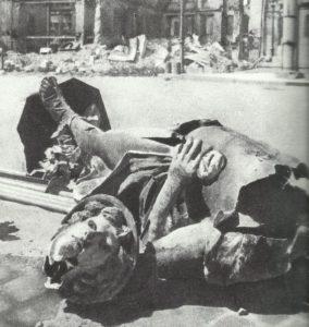 zertrümmerte Metallstatue eines Merkurs vor der Ruine des Schwarzhäupterhauses