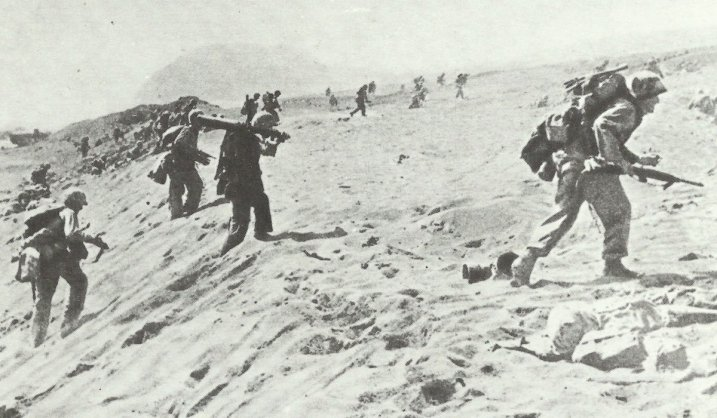 Marine schleppt Browning-MG über Strand von Iwo Jima