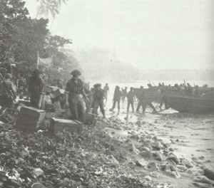 Neuseeländische Soldaten der zweiten Welle der Landungstruppen entladen Versorgungsgüter von Landungsbooten auf der Treasury-Insel.