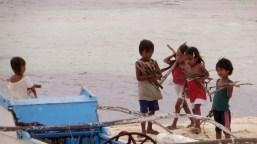 Kinder sammeln Treibholz für Schmuck in Haiform und Feuerholz