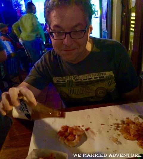 Mike enjoying fresh Gulf peel-and-eat shrimp with Crystal hot sauce