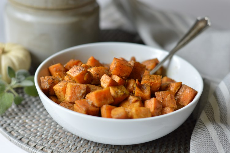 bowl of easy roasted sweet potatoes in a bowl with a serving spoon, on a woven placemat