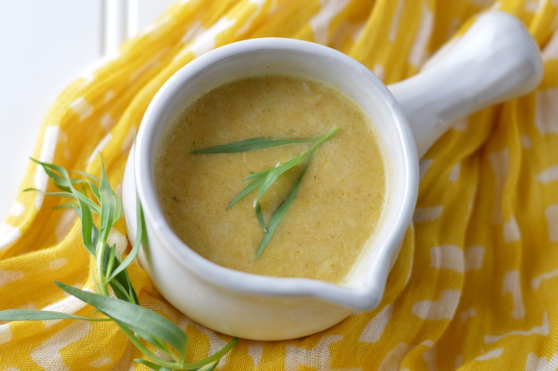 Light and bright butternut squash soup with lemon and tarragon in a white porcelain soup bowl