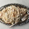 Shredded chicken yield from Falling-of-the-bone Crockpot Chicken recipe on a silver platter with serving fork