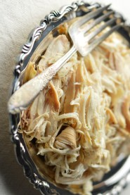 Shredded chicken yielded from Falling-off-the-bone Crockpot Chicken recipe on a silver platter with serving fork