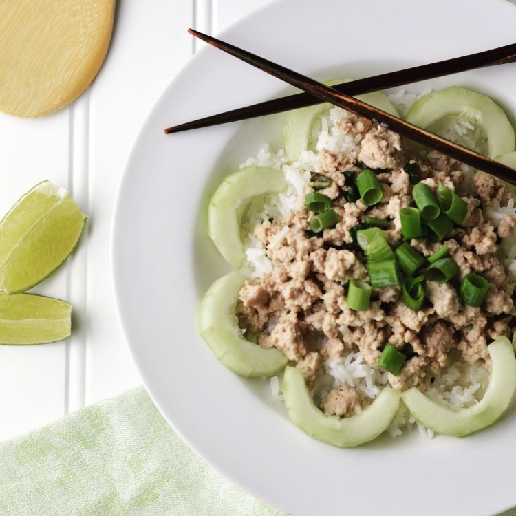 Asian-inspired ground turkey garnished with cucumber slices, green onions, and lime wedges