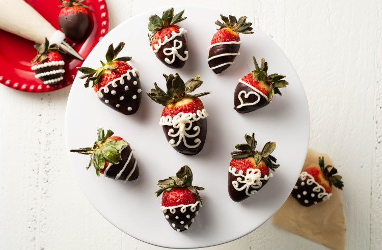 Several Carob-dipped Strawberries on a cake stand, piped with vanilla frosting in intricate designs