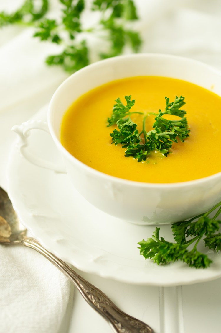 Closeup of Irish Carrot Soup in a dainty two-handled bowl surrounded by parsley