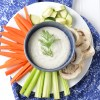 Raw vegetables surrounding a blue bowl filled with creamy, dairy-free ranch dressing, garnished with dill.