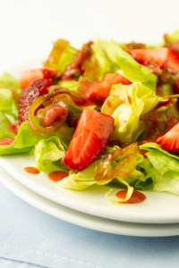 Closeup of salad of butter lettuce, caramelized onions, fresh strawberries drizzled with a strawberry balsamic vinaigrette