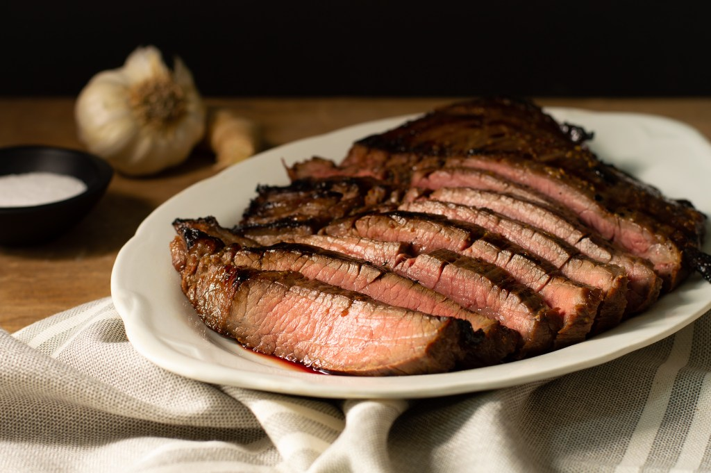 Flank Steak grilled medium rare on a white platter, juices showing