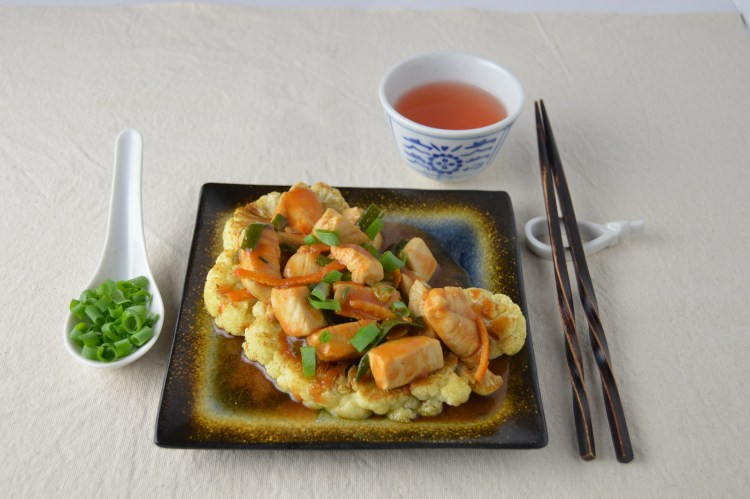 Orange Peel Chicken over Cauliflower Steak on a square plate with chopsticks