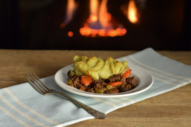 Intense Shepherd's Pie topped with mashed white sweet potatoes placed on a rustic board in front of a fire.