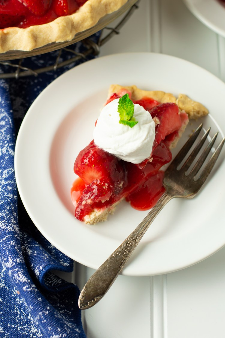Closeup of fresh strawberry pie topped with whipped coconut cream and a sprig of mint