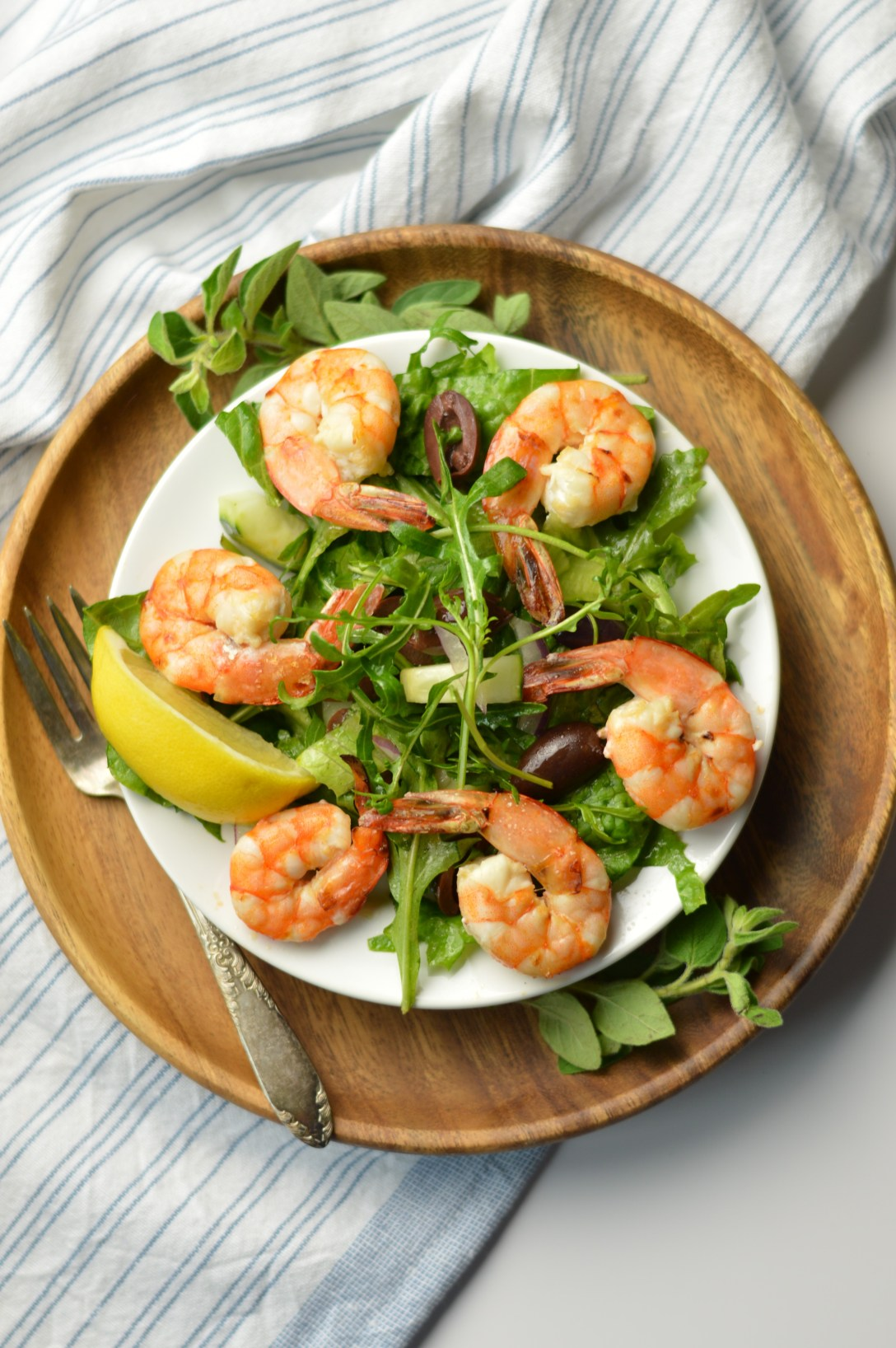 Mediterranean Salad with Shrimp and a lemon wedge on a white plate