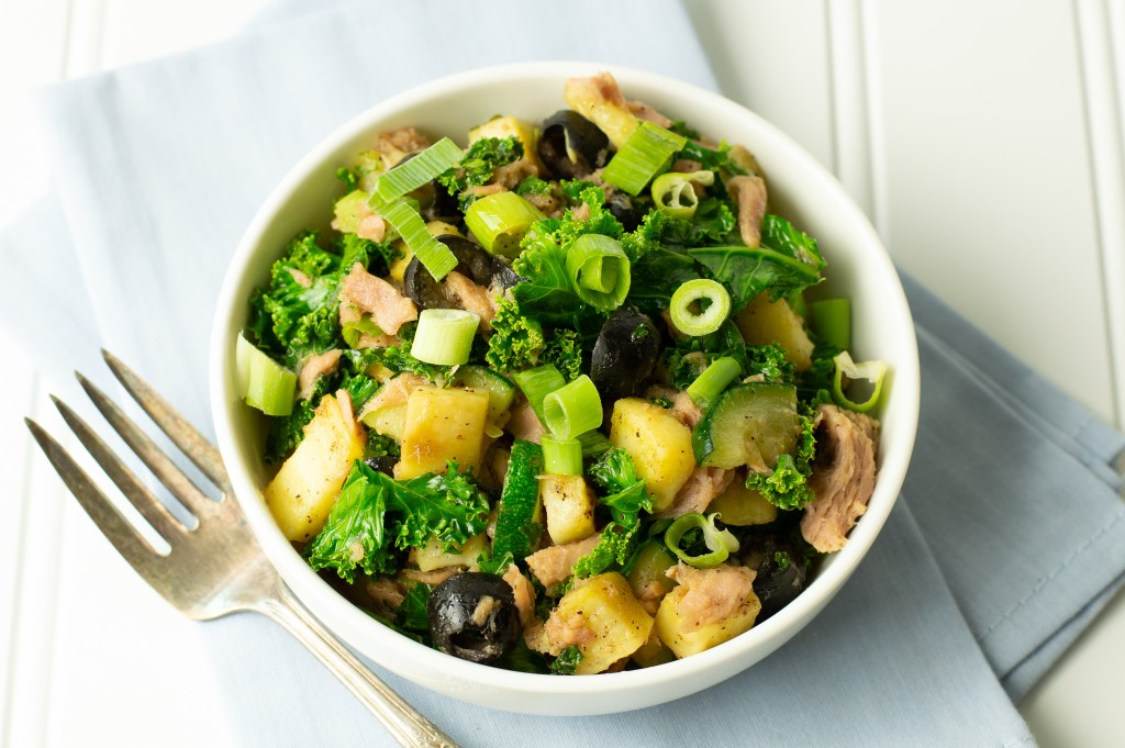 Tuna, kale, white sweet potatoes, black olives, green onions in a smooth white bowl.
