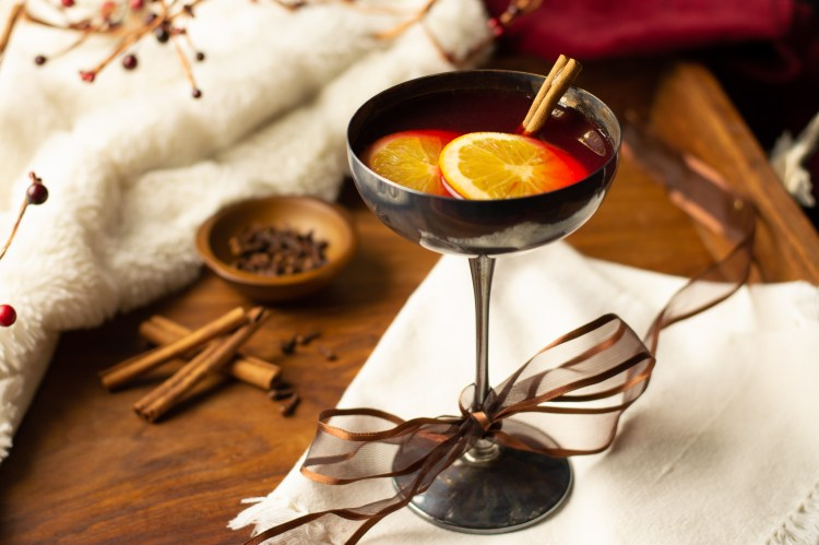 spiced pomegranate wassail garnished with two orange wheels and a cinnamon stick in a spicy winter scene