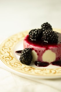 Closeup of Blackberry Lemon Panna Cotta.  The blackberry sauce is running down the sides of the custard onto an elegant plate.