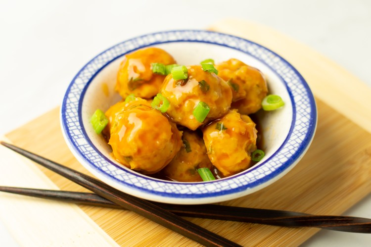 sweet and sour meatballs situated on top of a bamboo board with chopsticks
