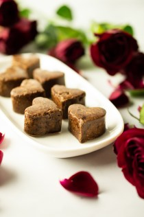 Heart-shaped Flavored Carob Candies romantically arranged midst roses and rose petals