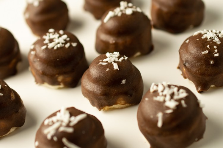 No-bake Banana Cookie Dough Bites drizzled with carob ganache and sprinkled with shredded coconut