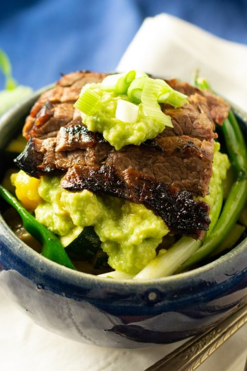 Skirt Steak Fajita Bowls topped with guacamole and green onions in an earthenware bowl next to a bunch of cilantro
