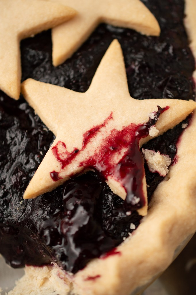 Closeup of one blueberry-smeared star made of crust atop the Blueberry Pie (AIP/Paleo)