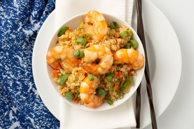"Bowl of Shrimp Fried ""Rice"" (AIP/Paleo) on a napkin and plate next to a pair of slender chopsticks"
