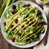Scene with Spinach Cherry Summer Salad topped with avocado cilantro dressing on a wooden table