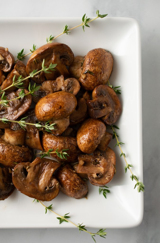 Flatlay view of Roasted Balsamic Mushrooms on a rectangular platter with sprigs of fresh thyme
