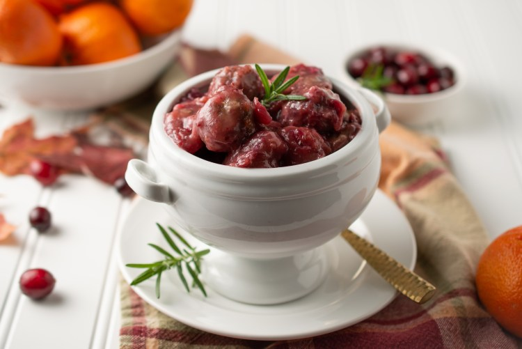 Scene with Cranberry Orange Meatballs in a footed bowl topped with rosemary near bowls of oranges and fresh cranberries