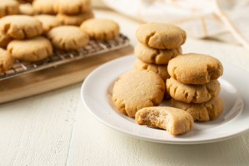 Scene of Vanilla Shortbread Cookies (AIP/Paleo), some on a plate, some on a cooling rack, and one with a bite missing.