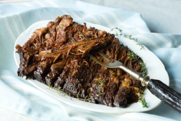 Tender & Tangy Brisket (AIP/Paleo) garnished with fresh thyme on a platter with a rustic meat fork