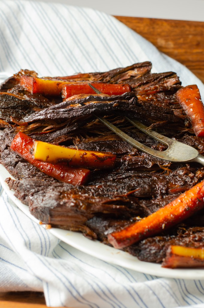 Tender & Tangy Brisket (AIP/Paleo) on a platter with roasted parsnips and carrots