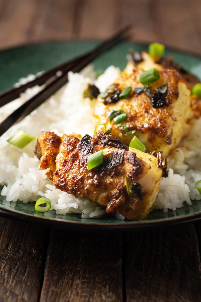 Closeup of Gingered Cod (AIP/Paleo) over white rice garnished with sliced green onions