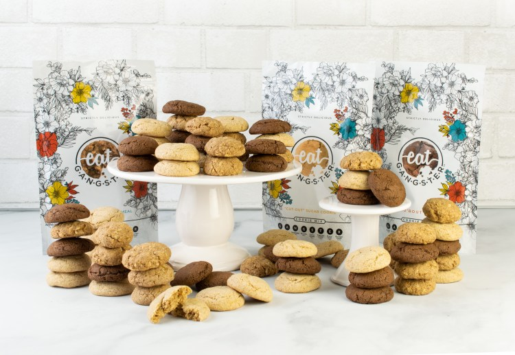 For AIP Gift Ideas: a kitchen scene of Eat Gangster cookies of three varieties on two different cake stands.  The mix bags are nearby.