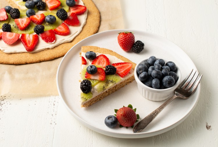 Vanilla Cookie Pizza (AIP/Paleo) in a scene.  There is a whole pizza to the side, and a white plate with one piece on it, covered in fruit with a small dish of blueberries nearby.