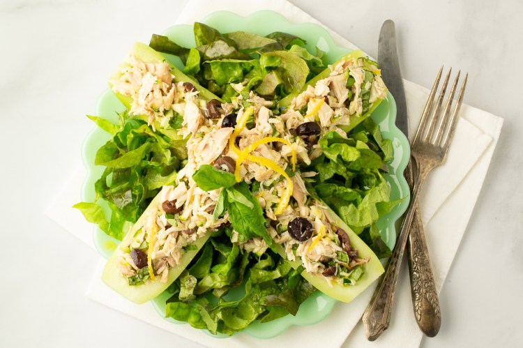 Overhead view of Mediterranean Chicken Salad (AIP/Paleo) in cucumber boats on a bed of lettuce. It sits on a scalloped plate with a knife and fork nearby.