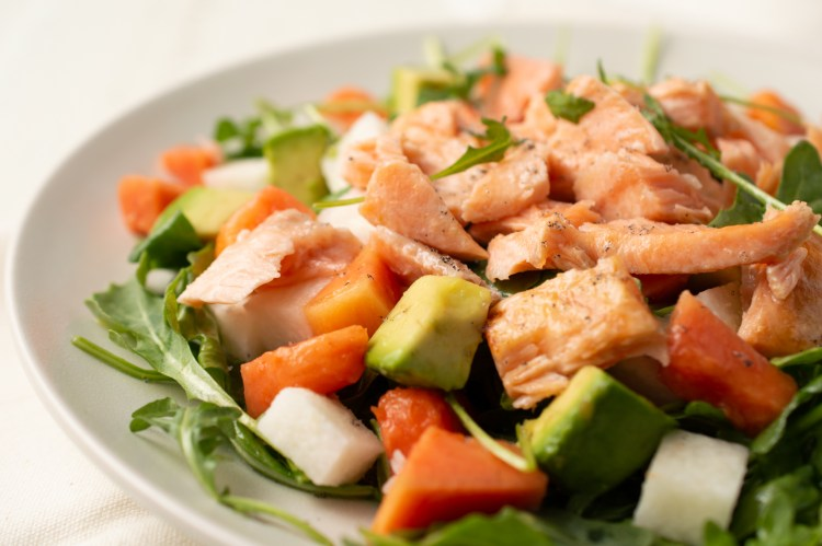 Closeup of Tropical Salmon Salad w/Vanilla Citrus Dressing. It sits on a cream-colored plate and napkin.