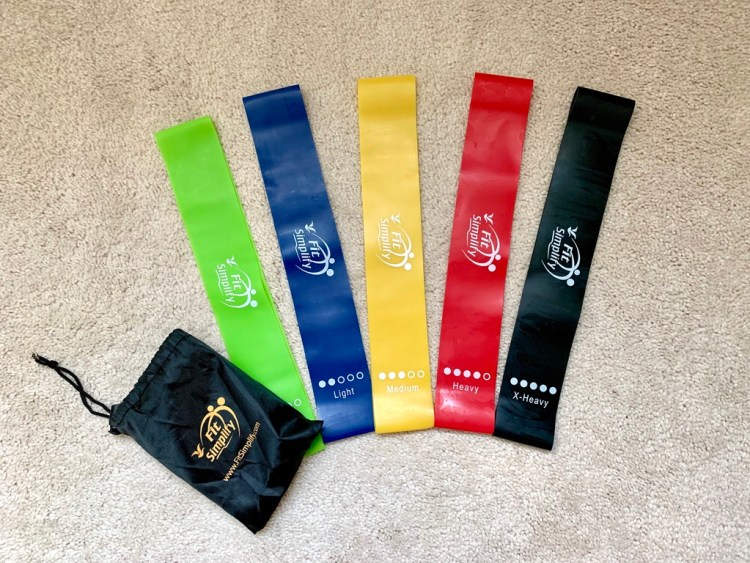 A grouping of compact exercise bands in varying levels of resistance is on a carpeted floor with their travel pouch nearby.