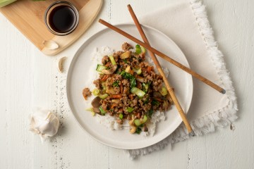 Easy Pork Stir-fry (AIP/Paleo) in a scene. It sits atop white rice on a rimmed dish with bamboo chopsticks. There is a bamboo cutting board with bow choi, garlic, and a small bowl of coconut aminos nearby.